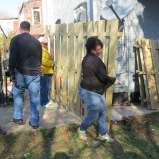 Fences being carried to the side of the house to await being put up.